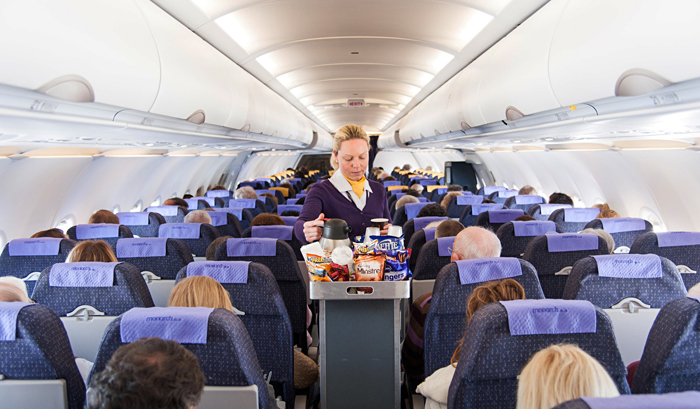 Monarch Airlines air stewardess serving snacks from the drinks trolley, England,